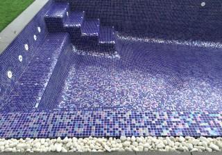 Piscina con revestimiento nacarado azul, banco y escalera