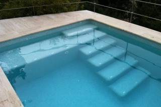 Piscina con escalera con playa
