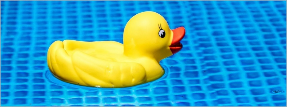 Patito de goma sobre agua cristalina de piscina